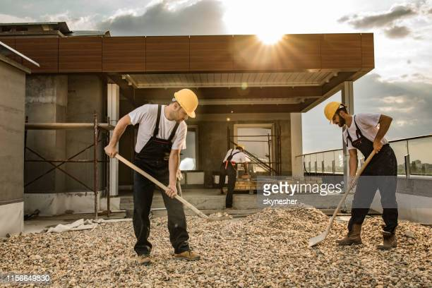 construction workers shoveling gravel while working on a penthouse balcony. - gravel stock pictures, royalty-free photos & images