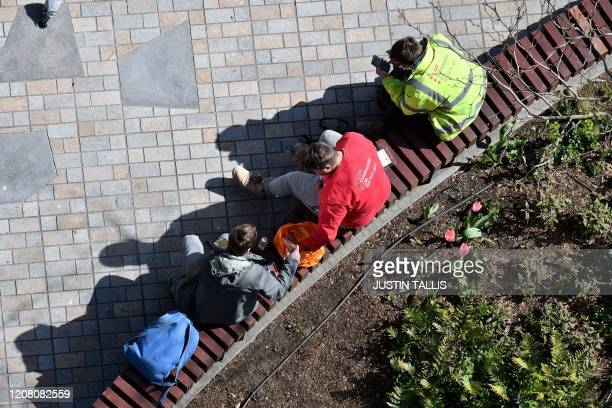 Construction workers sit on a bench as they have a bite to eat at Nine Elms in south London on March 24 as Britain's Chancellor of the Duchy of...