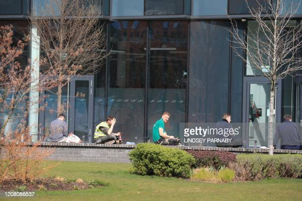 Construction workers sit on a wall at lunch observing social distancing in Leeds northern England on March 24 2020 after Britain ordered a lockdown...