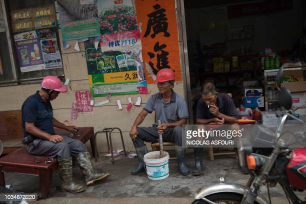 Construction workers smoke outside a store one day after Typhoon Mangkhut hit Yangjiang in China's Guangdong province on September 17 2018