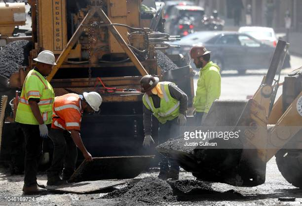 Construction workers smooth tar as they pave a road on October 5, 2018 in San Francisco, California. Newly released data by the Labor Department on...