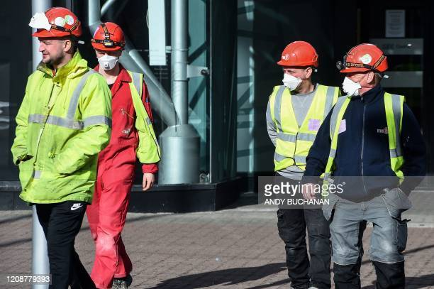 Construction workers, some wearing face masks, work at the Scottish Events Campus in Glasgow, on April 1 which has been transformed into a field...