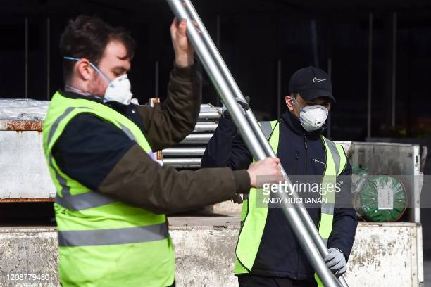 Construction workers, some wearing face masks, work at the Scottish Events Campus , which includes the SSE Hydro, in Glasgow, on April 1 as it is...
