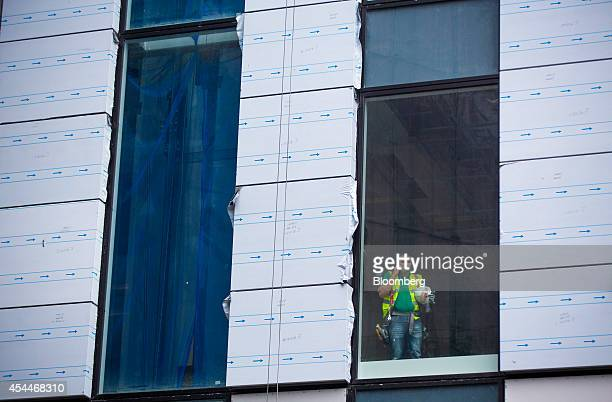 A construction workers speaks on a mobile handset as he stands by a window in UBS AG's new office complex at No 5 Broadgate in London UK on Monday...