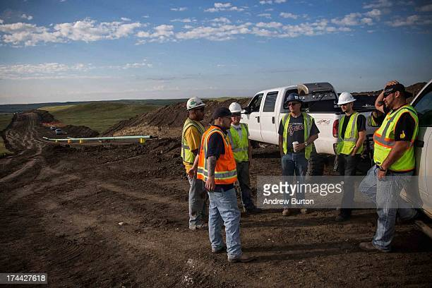 Construction workers specializing in pipelaying chat before work on July 25 2013 outside Watford City North Dakota North Dakota is currently...