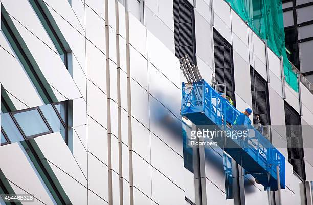 Construction workers stand in a hoist as they work outside the site of UBS AG's new office complex at No 5 Broadgate in London UK on Monday Sept 1...