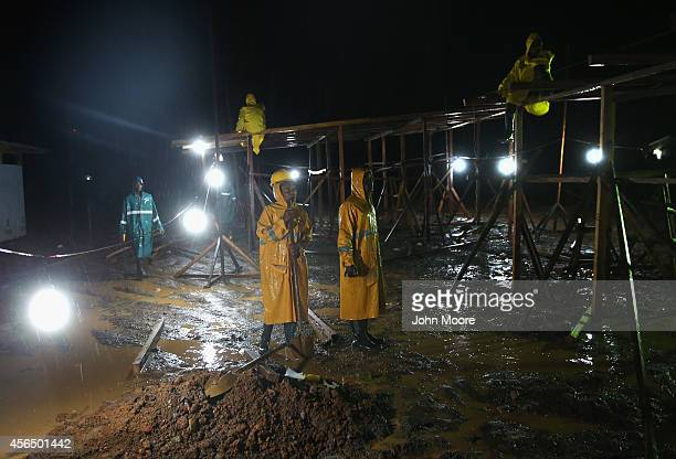 Construction workers stand in the rain while building a new Ebola isolation and treatment center overnight on Ocober 2 2014 in Monrovia Liberia Work...