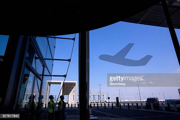 Construction workers stand outside Berlin Brandenburg International Willy Brandt Airport in Schoenefeld Germany on Monday May 3 2016 The massively...