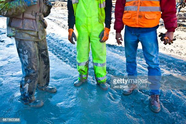 construction workers standing at a muddy jobsite - workers compensation stock pictures, royalty-free photos & images