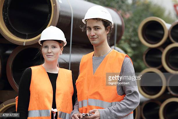 construction workers standing in front of pipes - sigrid gombert stock-fotos und bilder