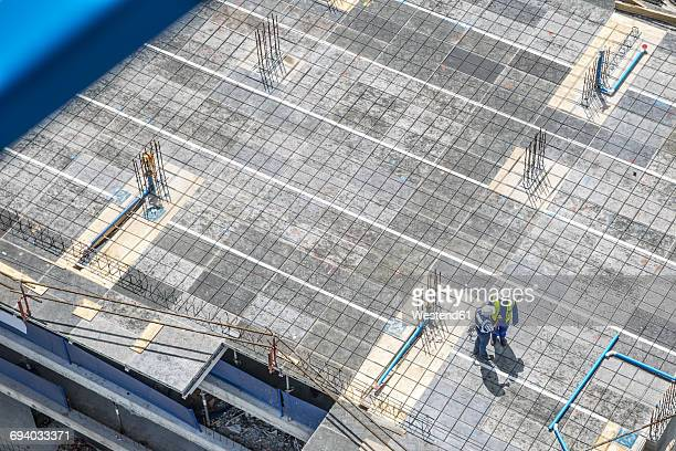 Construction workers standing on foundation, talking