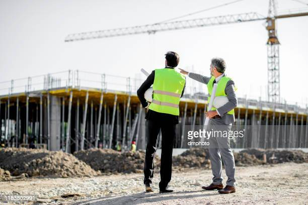 construction workers, supervisor, or engineer talk at job site - real estate developer stock pictures, royalty-free photos & images