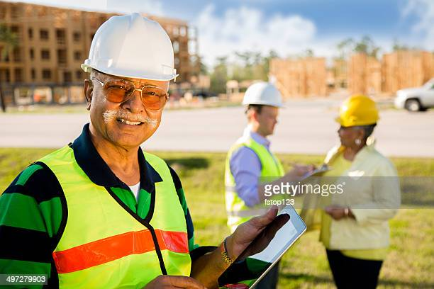 construction workers, supervisors talk at job site. digital tablet. - real estate developer stock pictures, royalty-free photos & images