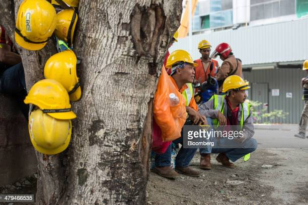 Construction workers take a break in Kuala Lumpur, Malaysia, on Tuesday, March 18, 2014. Malaysia, aspiring to become a developed nation in six...