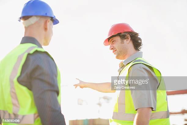 サイトでの工事について話す作業員 - 自己主張 ストックフォトと画像
