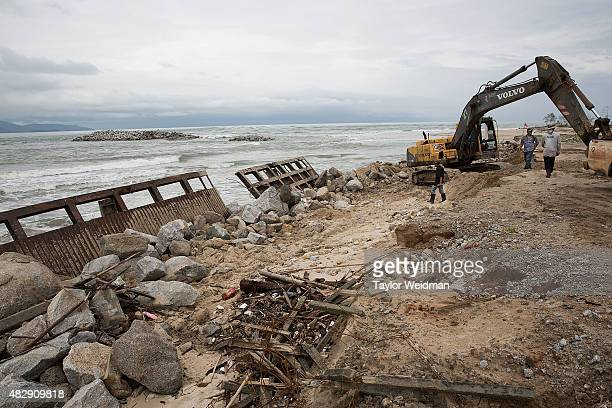 Construction workers try to fix a broken piece of equipment while working on the construction of a small interim port inside the planned Dawei SEZ on...