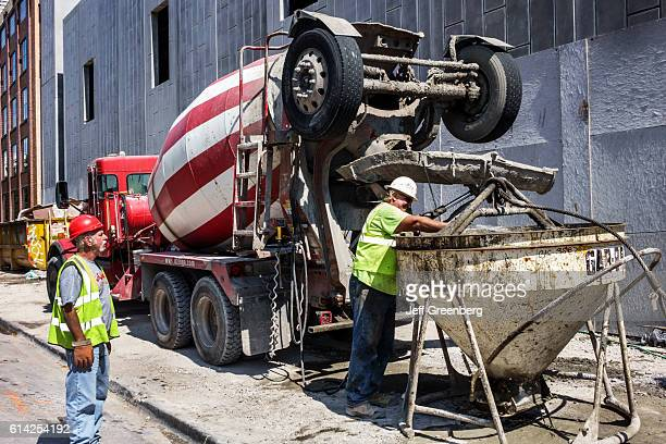Construction workers using cement mixer in Chicago