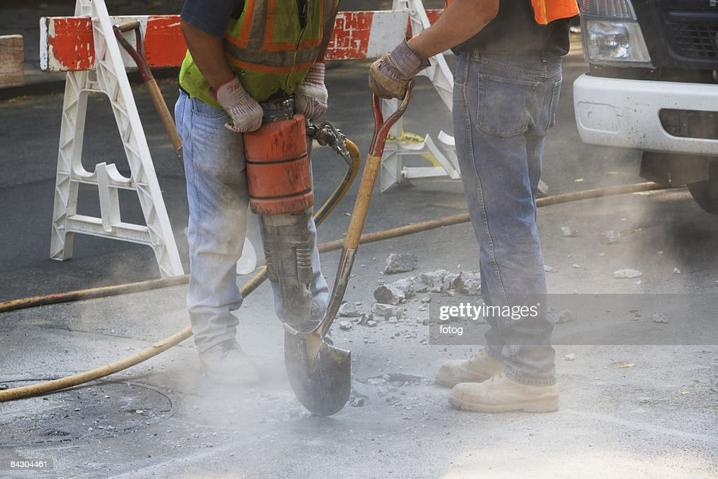 Construction workers using jackhammer and shovel : Stock Photo