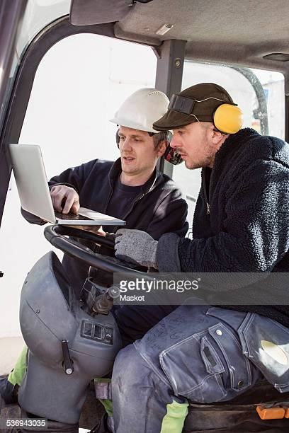 Construction workers using laptop in excavator