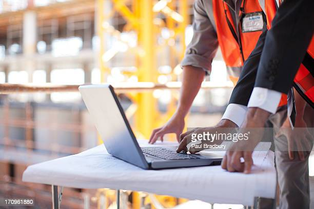 Construction workers using laptop on construction site