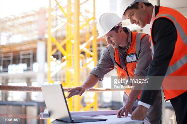 construction workers using laptop on construction site - computer software stock pictures, royalty-free photos & images