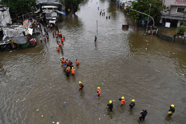 Construction workers wade along a waterlogged street following a heavy monsoon rainfall in Mumbai on July 16, 2021.