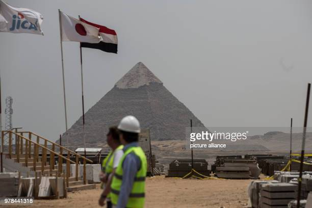 Construction workers walk at the construction site of the Grand Egyptian Museum backdropped by the Great Pyramid of Khufu in Giza Egypt 26 April 2018...