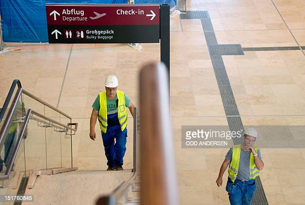 Construction workers walk at the main checkin hall of the BerlinBrandenburg International airport aka Willy Brandt Airport is seen during a visit to...