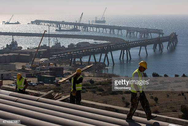 Construction workers walk on pipes as a partially completed fuel transportation jetty and the Mediterranean Sea are seen beyond at the VTTV oil...