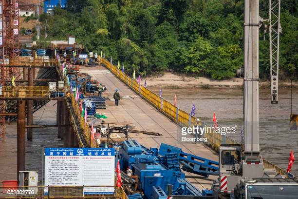 Construction workers walk on the Luang Prabang railway bridge a section of the ChinaLaos Railway built by the China Railway Group Ltd stand under...