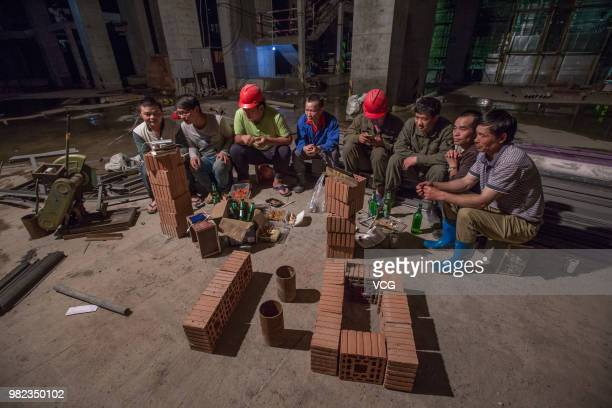 Construction workers watch 2018 World Cup group B match between Portugal and Morocco on a smartphone at a construction site on June 20 2018 in...