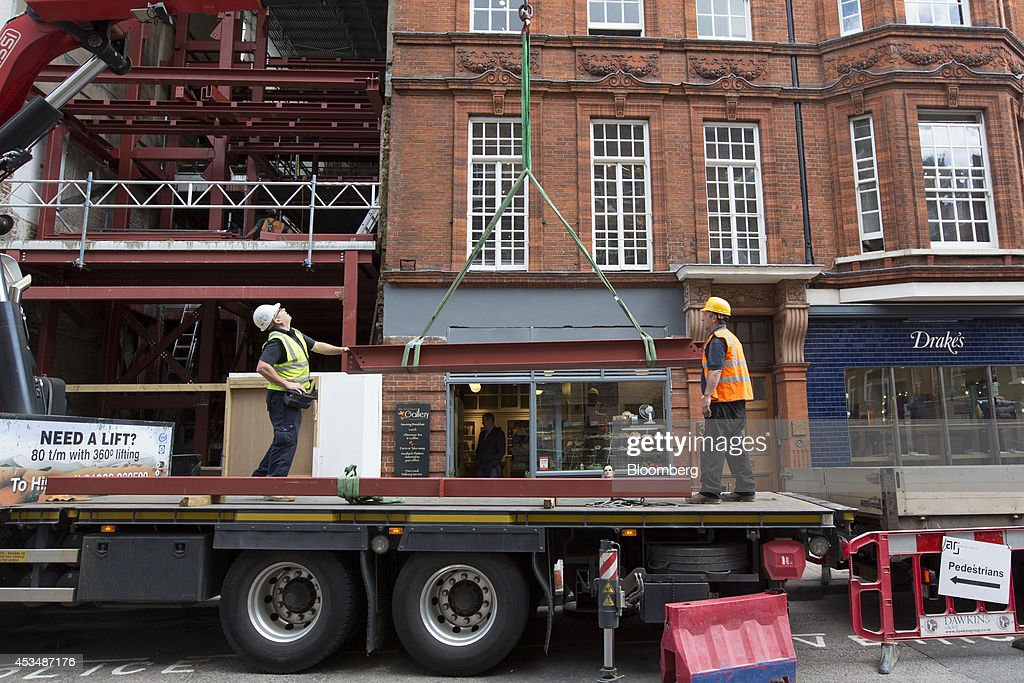 Construction workers watch as a crane lifts metal girders from a truck, outside commercial real estate buildings that form part of the Pollen Estate, on Savile Row in London, U.K., on Monday, Aug. 11, 2014. Norway's sovereign wealth fund, Norges Bank Investment Management, the world's largest, bought a stake in the Pollen Estate in London's Mayfair district for 343 million pounds ($576 million), expanding its property holdings in the U.K. capital. Photographer: Jason Alden/Bloomberg via Getty Images