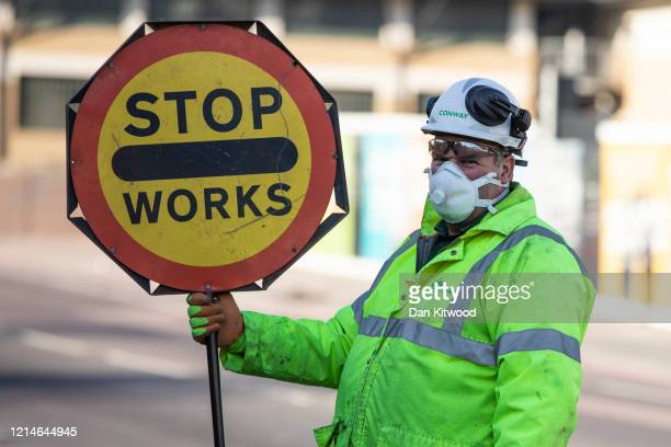 Construction workers wear masks and maintain social distancing as they continue working on Battersea Park Road in Wandsworth south west London on...