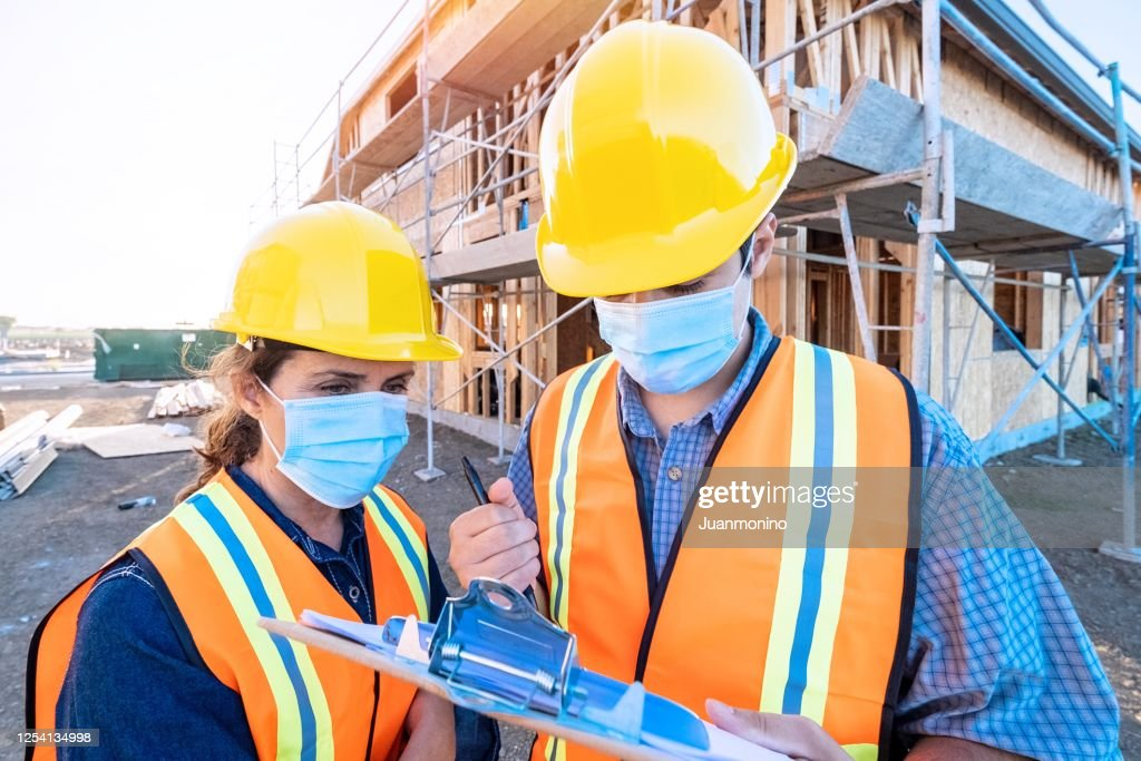 Construction workers wearing a protective face mask working at a construction site : Stock Photo