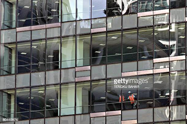 Construction workers wearing highvisibility orange vests clean the windows of a newlycompleted office highrise in downtown Kuala Lumpur on March 31...