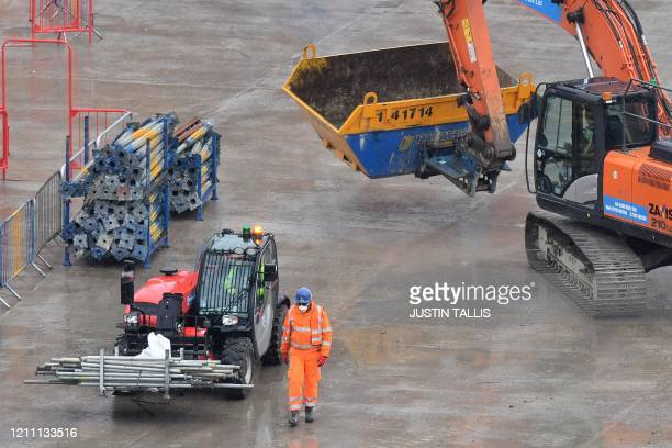 Construction workers wearing PPE including face masks build new apartments and retail complex at Nine Elms in south London on April 28 Prime Minister...