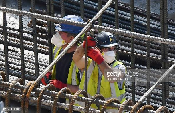 Construction workers wearing PPE including face masks build new apartments and retail complex at Nine Elms in south London on May 7 2020 UK output is...