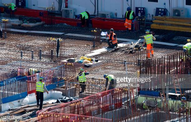 Construction workers wearing PPE , some including face masks, work to build new apartments and a retail complex at Nine Elms in south London on May...