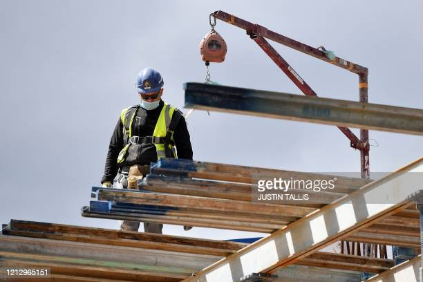 Construction workers wearing PPE some including face masks work to build new apartments and a retail complex at Nine Elms in south London on May 14...