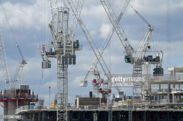 Construction workers wearing PPE some including face masks work to build new apartments and a retail complex at the Battersea Power Station...