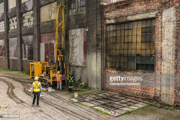 construction workers with a crane working on a facade of an old brick industry building with broken windows. - 公共物破壊 ストックフォトと画像