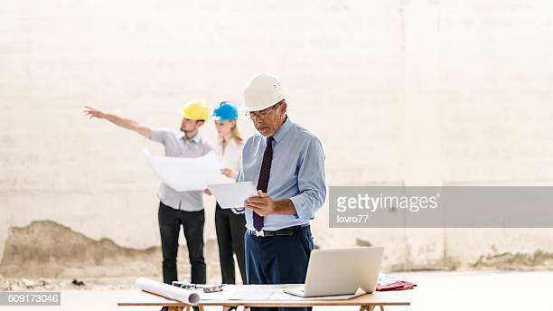 Construction workers with building plan