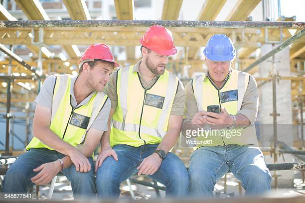 Construction workers with cell phone having a break