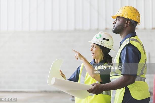 Construction workers with hardhats and blueprints