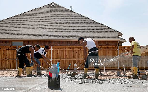 Construction workers work on the concrete slab for a new home is built to replace the one that was destroyed almost one year ago by a tornado on May...