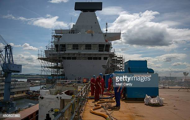 Construction workers work on the flight deck of HMS Queen Elizabeth aircraft carrier being built in Rosyth Dockyard on June 17 2014 in Rosyth...