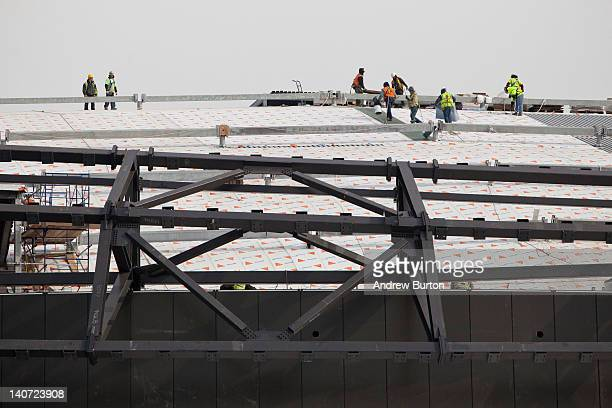 Construction workers work on the roof of the Barclay Center a sports arena and future home of the the National Basketball Association's New Jersey...