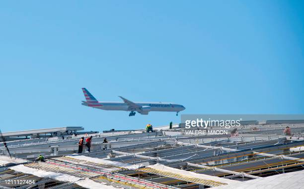 Construction workers work on the roof of the new stadium while a plane is approaching LAX airport amid the stay-at-home orders during the Covid-19...