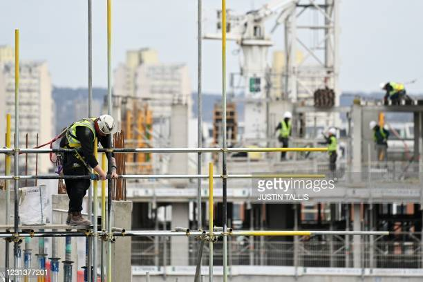 Construction workers work to build new apartments and a retail complex at Nine Elms in south London on February 25 as building sites remain open...