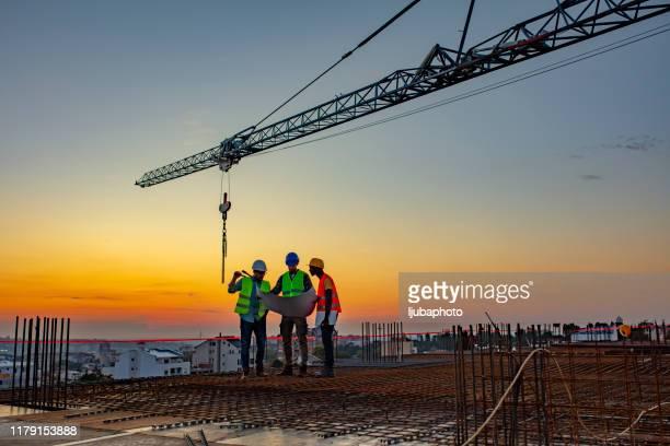 travailleurs de la construction travaillant sur un chantier de construction - métier du design photos et images de collection